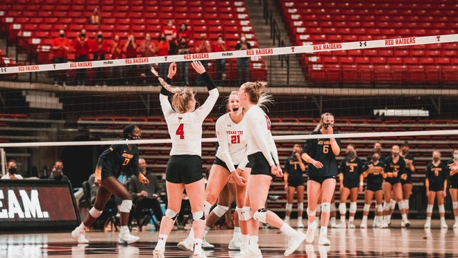 Lindsey Dodson (4), Brooke Kanas (21) and Alex Kirby celebrate during a regular-season, home-opening and Big 12 Conference match Thursday against West Virginia at United Supermarkets Arena. The Red Raiders won 25-17, 25-23, 25-22.