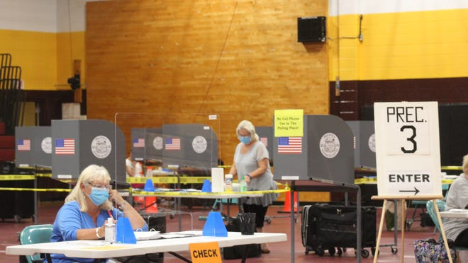 Poll workers in masks and behind plexiglass? It's a sign of the coronavirus times.