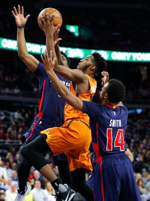 Phoenix Suns forward Derrick Jones Jr. drives between Detroit Pistons forward Stanley Johnson, rear, and guards Ish Smith during the first half of an NBA basketball game in Auburn Hills, Mich., Sunday, March 19, 2017.