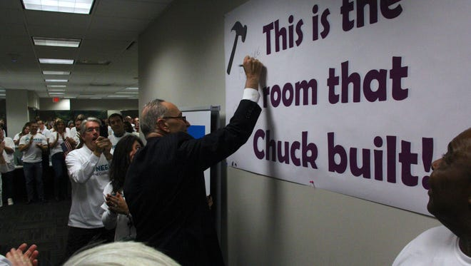 U.S. Sen. Charles Schumer autographs a sign inside Pioneer Credit Recovery's Big Flats facility Thursday. The company will add 300 new jobs after receiving a federal contract.