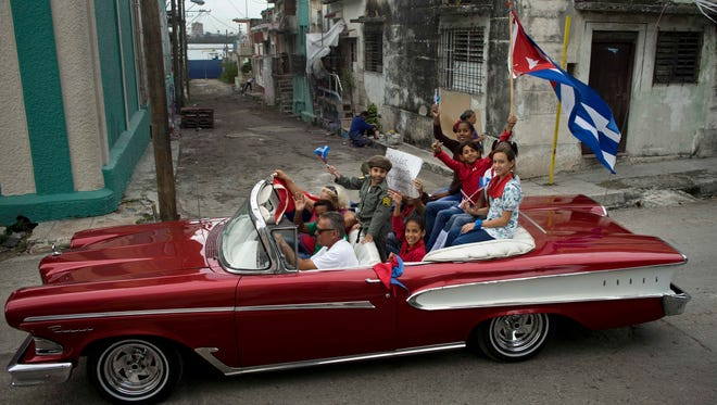 Cuban children, one dressed as Fidel Castro, ride on a classical car during a caravan marking the 57th anniversary of the arrival of Fidel Castro an his rebel army in Regla,  outskirts of Havana, Cuba, on Jan. 8, 2016.