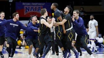 Graceland's Justin Harley, center, celebrates his game-winning overtime basket with teammates.