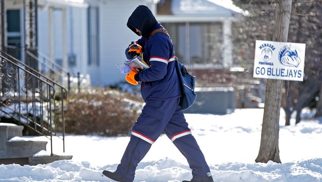 Mail carrier Jeff Simon braves the bitter temperatures Monday along Racine Street in Menasha.