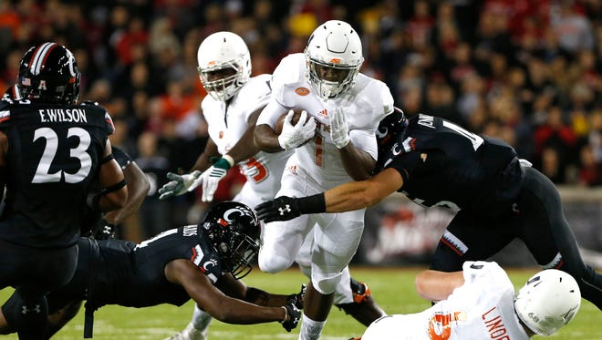 Miami Hurricanes running back Mark Walton (1) carries the ball as he is tackled by Cincinnati Bearcats linebacker Bryce Jenkinson (45) in the first half at Nippert Stadium.
