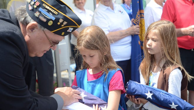 Jim Leslie, commander of American Legion Post 8, inspects American flags carried by 6-year-old Clara and 8-year-old Katarina Taylor during a flag retirement ceremony Saturday,