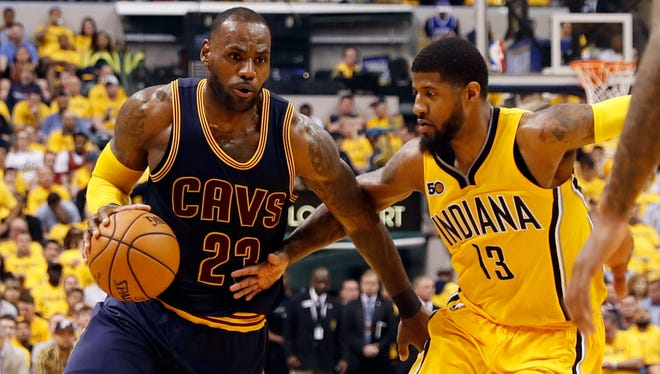 LeBron James drives to the basket against Paul George  in a 2017 game. The two NBA free agents could potentially sign with the same team.