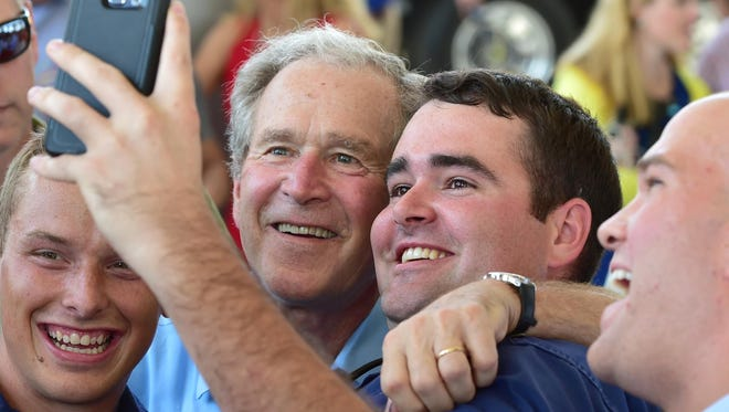 Former president George W. Bush and James Doughty take a selfie during Friday's Hurricane Katrina First Responder Rembrance ceremony in Barksdale Pavilion at Jones Park in Gulfport.