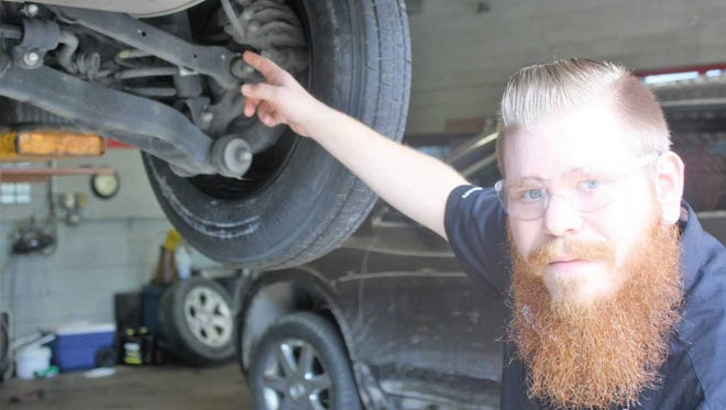Belle Tire assistant manager Jesse Skardoupos examines a recently damaged suspension.