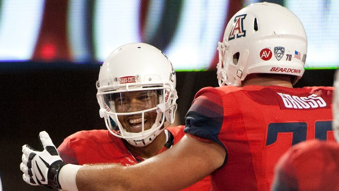 Sep 19, 2015: Arizona Wildcats quarterback Brandon Dawkins (13) and offensive lineman T.D. Gross (70) celebrate after a touchdown during the fourth quarter against the Northern Arizona Lumberjacks at Arizona Stadium. Arizona won 77-13.