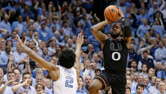 Miami's Ja'Quan Newton (0) shoots the game-winning shot as time expires while North Carolina's Joel Berry II (2) defends during the second half of an NCAA college basketball game in Chapel Hill on Tuesday. Miami won 91-88.