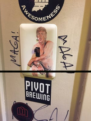 """A switch plate in the men's restroom at Against The Grain with a replica of the 2016 painting """"Make America Great Again,"""" a nude with the face of Donald Trump by artist Illma Gore. The CJ has added a black bar to cover the exposed genitalia."""
