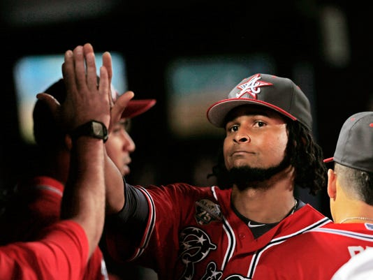 Atlanta Braves starting pitcher Ervin Santana is greeted in the dugout by teammates after being relieved in the eighth inning of a baseball game against the Arizona Diamondbacks in Atlanta, Friday, July 4, 2014. (AP Photo/John Bazemore)