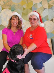 "Parsley, a therapy dog with Hospice of Health First, sits with Deb Peterson and volunteer Shelia Wilson at a ""Giving Tuesday"" event."
