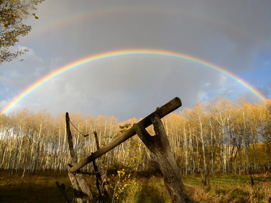 A twin rainbow frames gold-leafed aspens on a Colorado