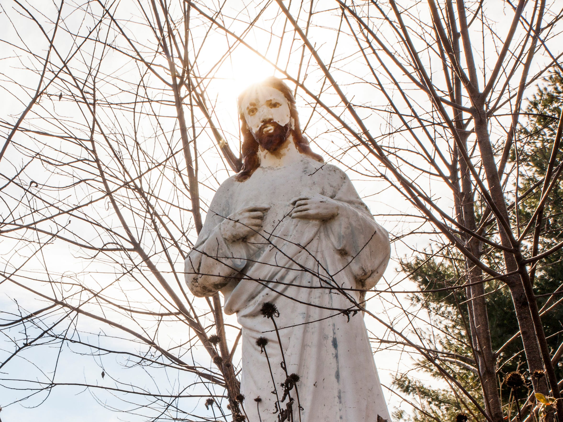 A statue of St. Luke stands outside of the abandoned