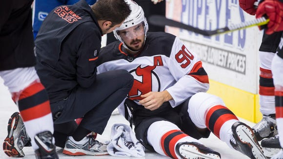 New Jersey Devils' Marcus Johansson, of Sweden, is tended to by a trainer after crashing head first into the boards during the first period of an NHL hockey game against the Vancouver Canucks, Wednesday, Nov. 1, 2017 in Vancouver, British Columbia.   (Darryl Dyck/The Canadian Press via AP)