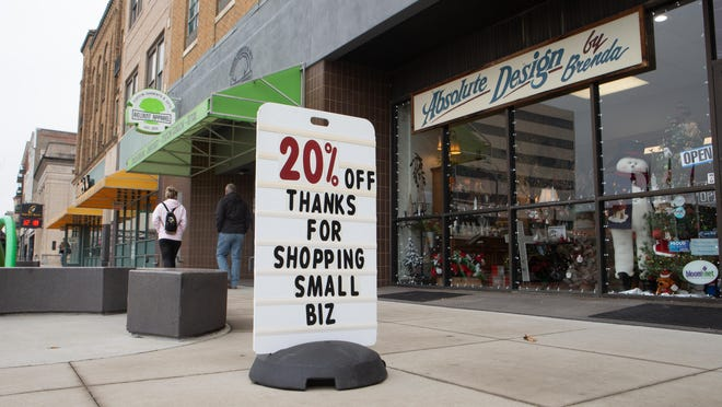 A sign outside of Absolute Design by Brenda in Topeka encourages customers to shop local this holiday season. Small businesses in Kansas are starting to ponder lawsuits seeking damages for losses suffered due to COVID-19 closures.