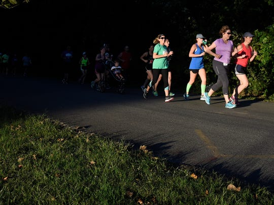 Members of Team 13 run through Wesselman Park in Evansville Tuesday.  The team of hundreds of runners are using the training program to prepare for the Evansville Half Marathon in October.