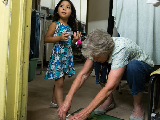 Volunteer Sharon White, right, helps Janhay Avila,