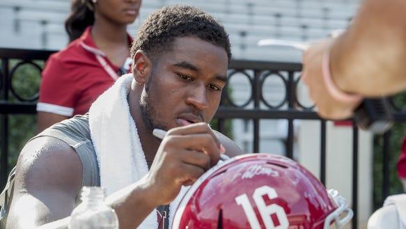 Alabama linebacker Shaun Dion Hamilton (20) signs autographs