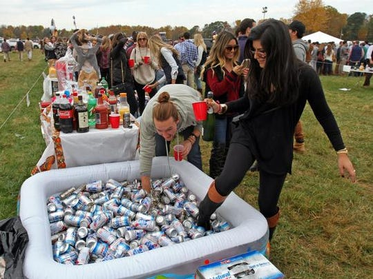 Chris Hughes, left, of Newport, R.I., and Kimya Sharif of Bernardsville and their friends, have plenty of beer in the kiddie pool, at the annual Far Hills Race Meeting that includes plenty of tailgating and horse racing, October 18 2014 Warren NJ.