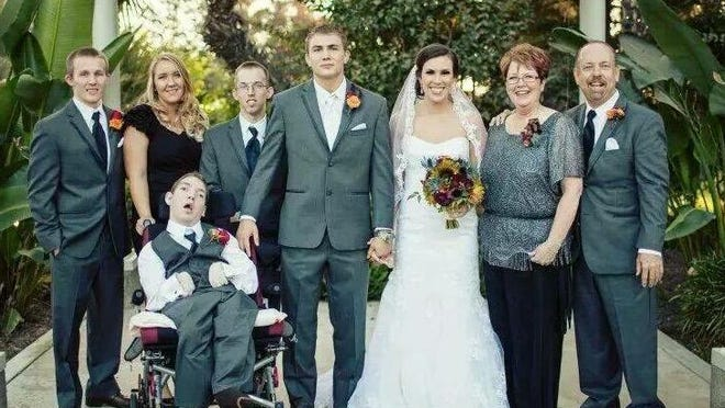 In every family picture, Cody always has his hand protectively on Jacob. Here at Cody's wedding is the entire family: Keith, his fiancée Bailey, Josh, Cody, Cody's wife Jackie, Debbie and Mike with Jacob.