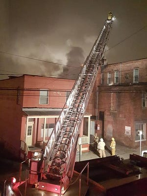A fire ladder stretches above a burning apartment building in downtown Bath.