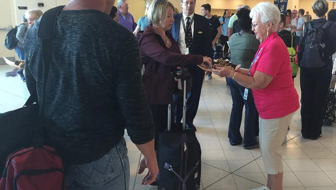 VCB volunteer tourism ambassador Nancy Feyh serves cookies to passengers at Southwest Florida International Airport.