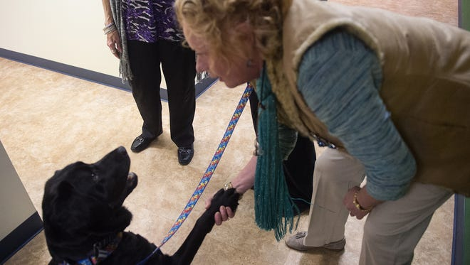 Buster lifts his paw to shake with Carol Connor, director of public relations and development for TrueNorth Wellness, on March 25, 2015.
