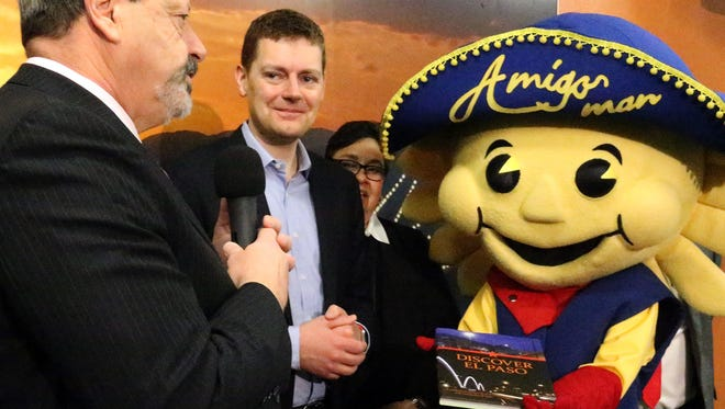 El Paso mayor Oscar Leeser, left, with help from the Amigo Man presents a book about El Paso to Brian Davis, center, vice president for marketing at Allegiant Air Tuesday at City Hall. Davis announced the company will begin non-stop flights from El Paso to Orlando, Florida in late May.