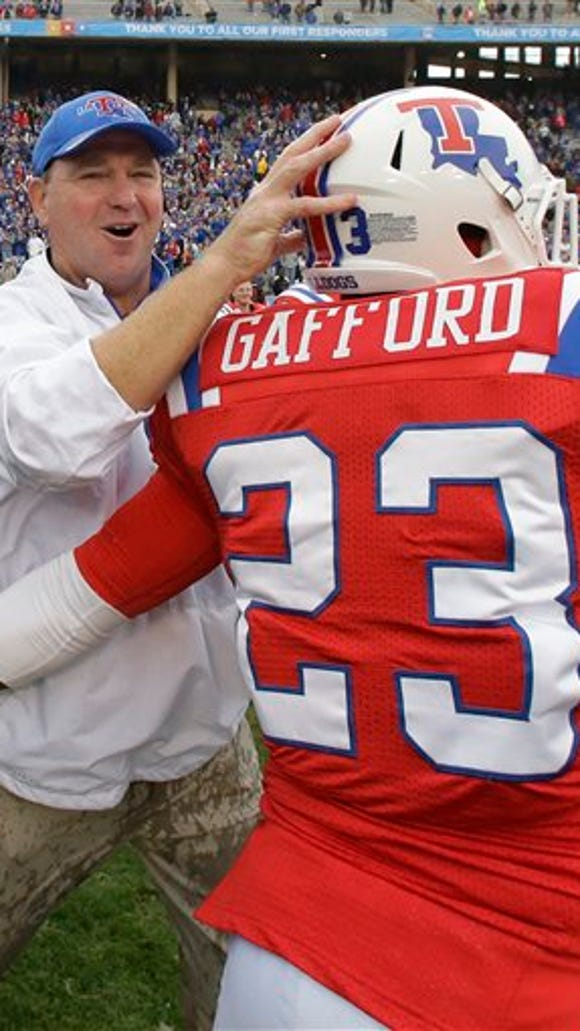 Louisiana Tech head coach Skip Holtz celebrates with running back Jay Gafford (23) after the Heart of Dallas Bowl NCAA college football game against llinois  Friday, Dec. 26, 2014, in Dallas. (AP Photo/LM Otero)