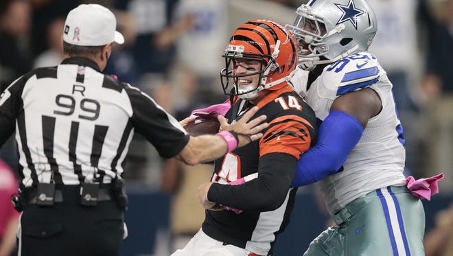 Cincinnati Bengals quarterback Andy Dalton (14) reacts as Dallas Cowboys defensive tackle Cedric Thornton (92) hangs onto him for longer than he expected on a sack in the second quarter during the NFL football game between the Cincinnati Bengals and the Dallas Cowboys, Sunday, Oct. 9, 2016, at AT&T Stadium in Arlington, Texas.