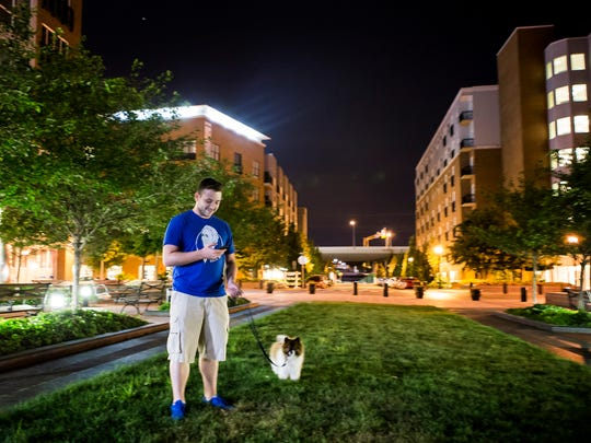 Mike McClellan plays Pokemon Go as he takes his Pomeranian, Chief, out to do his business outside Justison Landing on Tuesday night.