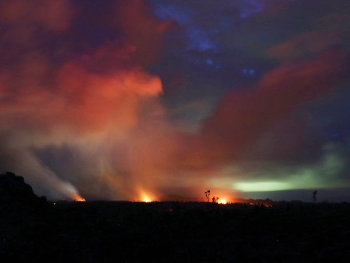 Lava shoots into the night sky from active fissures