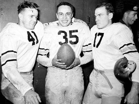 """FILE - In this Nov. 20, 1946, file photo, Army's, from left, Glenn Davis, Felix """"Doc"""" Blanchard and Arnold Tucker (17) pose after they defeated Navy 21-18 in a football game in Philadelphia, Pa. A little thing like being on opposite sides in one of the most storied college football games ever played couldn't even come between Pete Williams and Arnold Tucker, a pair of Miami High grads who had starring roles in the 1946 Army-Navy game, one that Grantland Rice called the greatest ever played.  (AP Photo/File"""