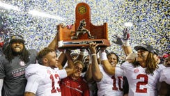 Alabama celebrates with its trophy after winning the