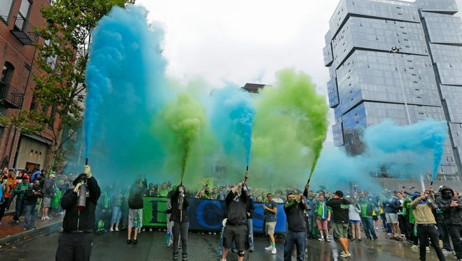 Members of the Emerald City Supporters set off smoke effects during the traditional March to the Match before an MLS soccer match between the Seattle Sounders and the Portland Timbers, Sunday, Aug. 30, 2015, in Seattle.
