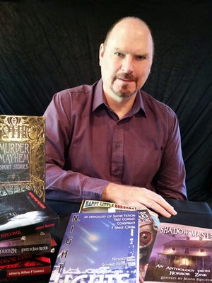 Dean Wild, of Brownsville, poses among a collection of short story anthologies containing his work.