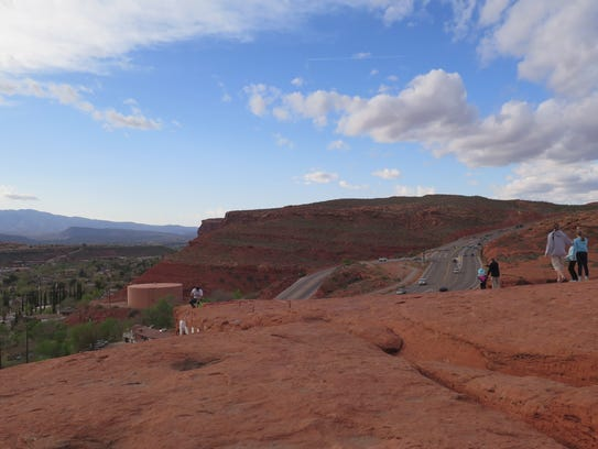 """Visitors scramble across the """"Sugar Loaf"""" rock at Pioneer Park in St. George. Daylight Saving Time, which starts Sunday, meant longer-lasting sunlight for evening visitors to the popular cliffside park."""