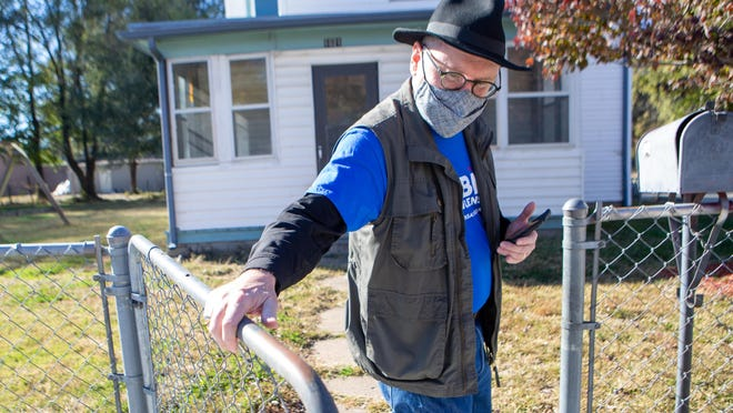 Tobias Schlingensiepen, Democratic candidate for the Kansas Senate 18th district, closes the gate behind him to a residence in North Topeka on Friday afternoon while campaigning. Schlingensiepen has been knocking on doors while wearing a mask and social distancing.