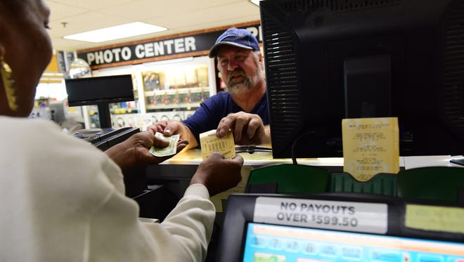 A clerk at Shoprite in Hackensack, sells a lottery ticket from the same machine that printed the winning $130M Powerball in Hackensack on Monday May 21, 2018.