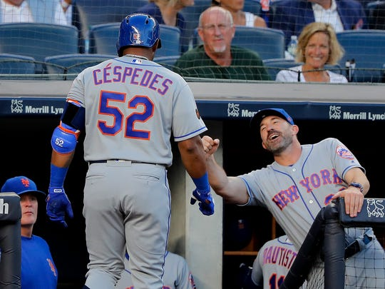New York Mets' Yoenis Cespedes (52) is congratulated by manager Mickey Callaway (36) after Cespedes hit a solo home run against the New York Yankees during the third inning of a baseball game Friday, July 20, 2018, in New York.