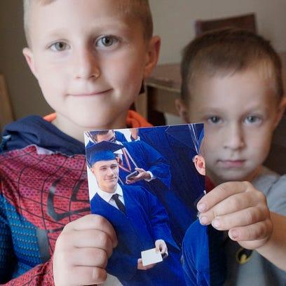 Collin Kosinski, 6, and Chad Kasbauer. 4, hold a photo