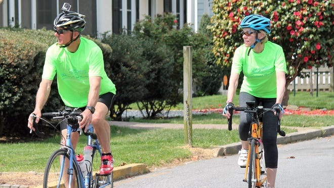 John and Pamela Eckenrode are one of about a dozen cyclists volunteering at the Coastal Delaware Running Festival. Their job is to keep the runners on course and safe.