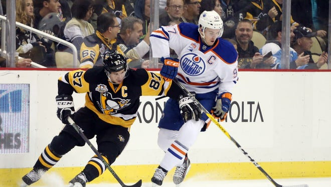 Oilers center Connor McDavid (97) controls the puck against Penguins center Sidney Crosby (87) during a November 2016 game.