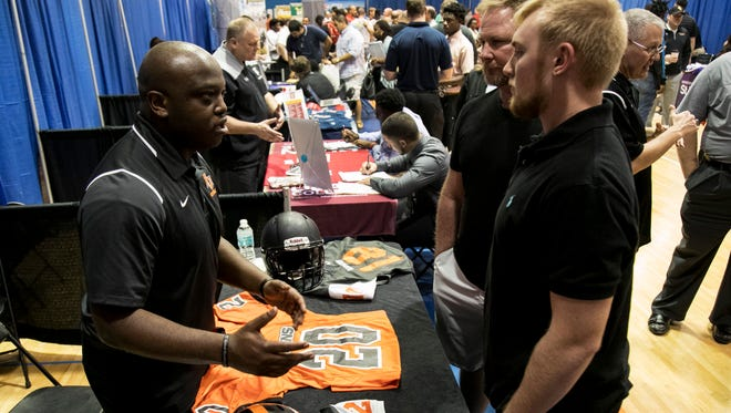 Frankie Buncik, a Venice High School student, and his dad Joe get information about Anderson University from offensive coordinator Tim Sanders at the Southwest Florida football recruiting fair at Cape Coral High School on Friday, Feb. 16, 2018.
