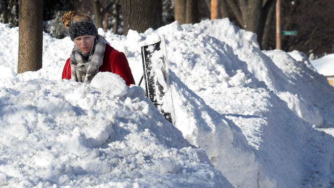 Lauren Rosengarden of Mount Prospect, Ill., digs out her driveway the day after a significant snowfall.