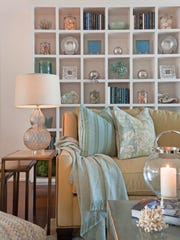 Displaying personal items in an organized and   balanced way, such as in a multicompartment shelving unit, can make a living room feel inviting and comfortable.
