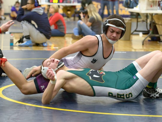 Pennfield's Chris Curtis works to avoid being pinned by Athens Rayden Roggow
