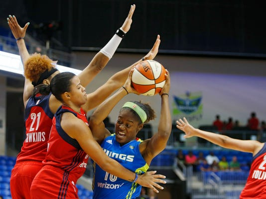 Dallas Wings guard Kaela Davis (10) looks to attempt a shot as she is defended by Washington Mystics forward Tianna Hawkins (21) and guard Natasha Cloud (9) during the first half of a WNBA basketball game in Arlington, Texas, Tuesday, June 6, 2017. (Vernon Bryant/The Dallas Morning News via AP)
